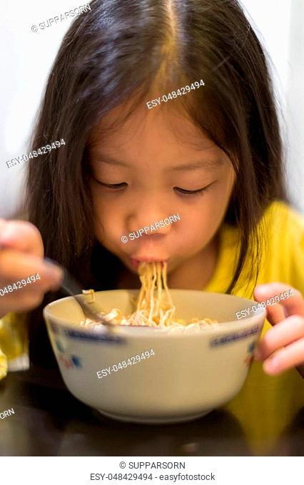 Hungry kid eating noodle or Chinese ramen