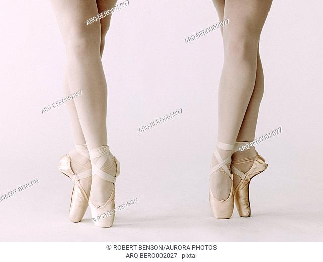 Low section of two ballet dancers standing side by side en pointe