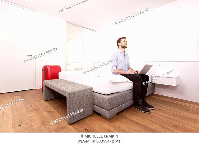 Man sitting with laptop on a hotel bed