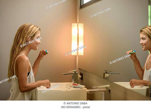 Young woman looking at bathroom mirror whilst brushing teeth
