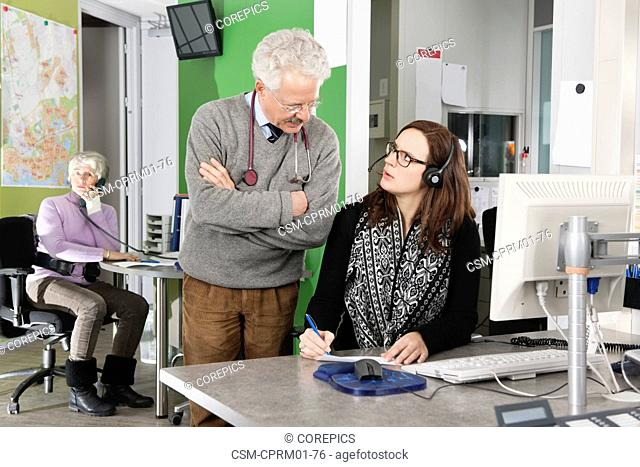 Doctor with stethoscope, discussing the planning and appointment list with a nurse and receptionist in a medical emergency call center in a hospital