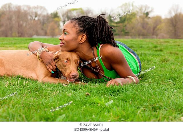 Young woman and her dog lying on grass