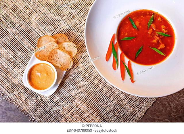 French fish soup Bouillabaisse served with pepper mayonnaise, toasted baguette and grated cheese. Selected focus on the upper part of the plate and the toasts