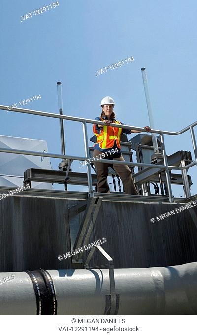 A female civil engineer, wearing a hard hat and a reflective orange vest, stands on a walkway in front of a water filtration system; Chapel Hill, North Carolina