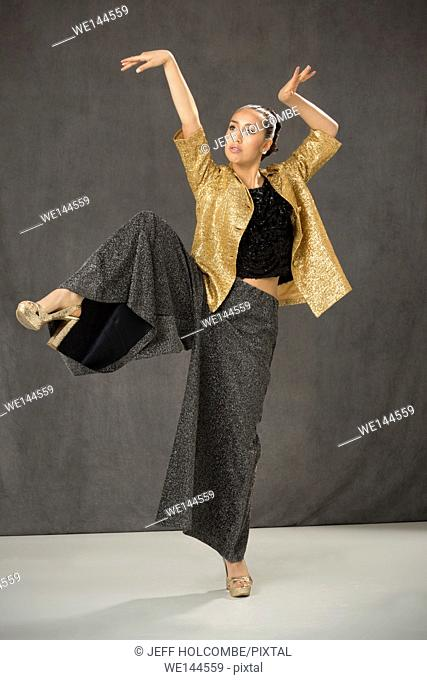 Young woman dancing in open gold jacket and baggy gray pants, one leg raised with white floor and gray background
