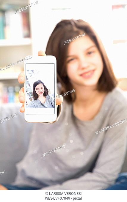Girl showing selfie on cell phone display