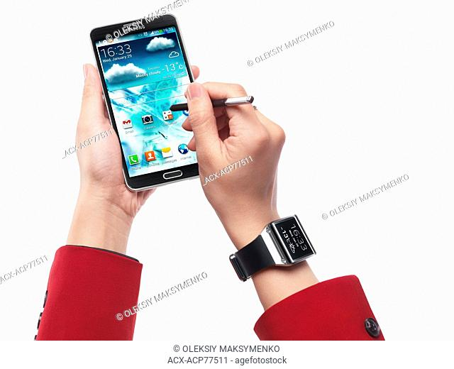 Woman wearing Samsung Galaxy Gear watch and using Galaxy Note III smartphone isolated on white background