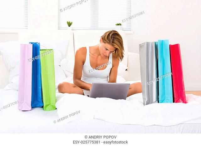 Young Woman Sitting On Bed Shopping Online On Laptop