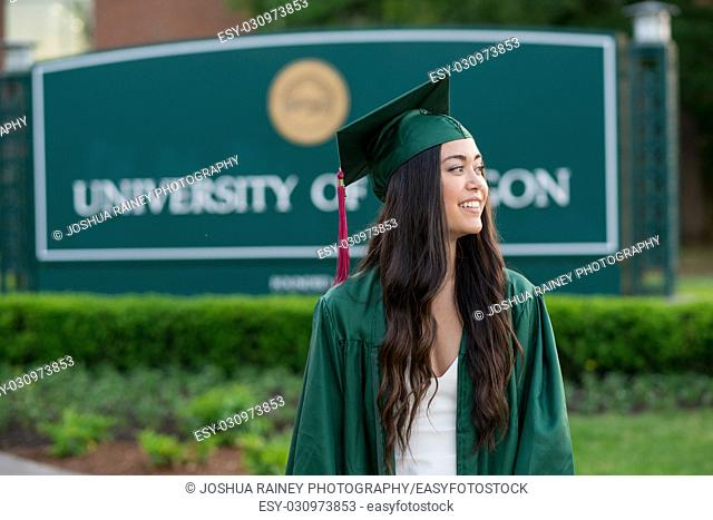 Female graduating student in her cap and gown with a blurred out college school sign in the background on a university campus during the Spring in Oregon