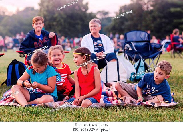 Group of adults and children, sitting outdoors, during 4th July celebrations