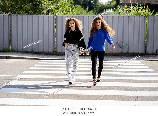 Twins walking on zebra crossing