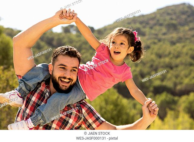 Smiling man playing with little daughter on his shoulders