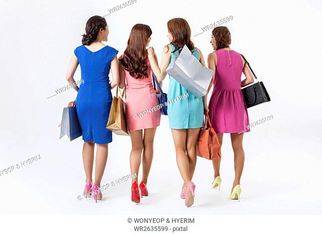 Back of four young female shopping buddies walking