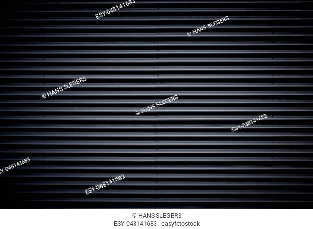 Wide shot of dark corrugated metal with bolts. Vignette added
