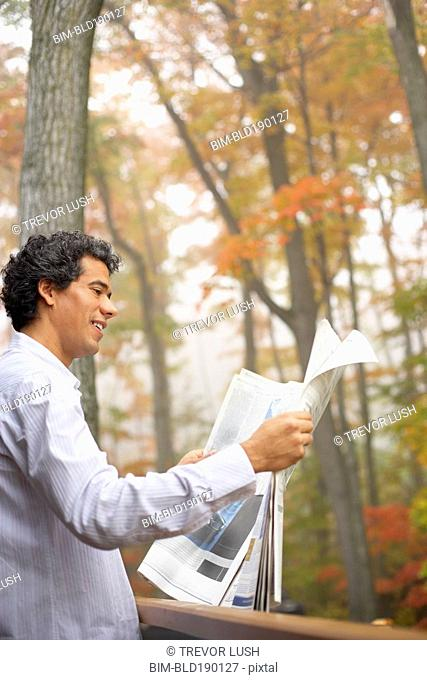 Man reading newspaper outdoors