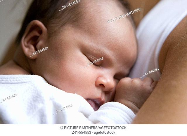 Baby sleeping on mothers arm