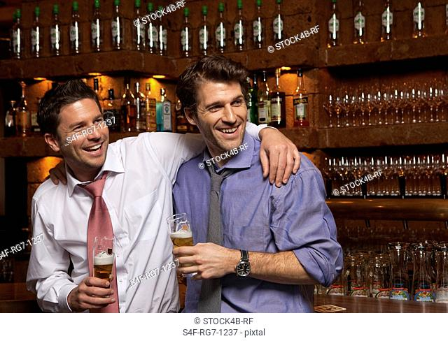 Two friends having a beer in a bar