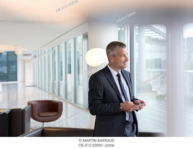 Businessman texting with cell phone in lounge