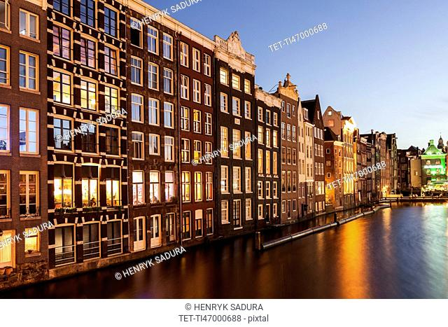 Buildings by canal at sunrise