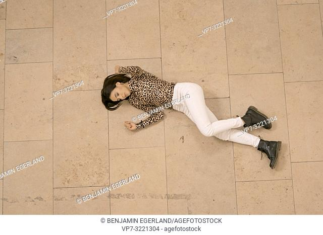 intimate view of woman laying on stone floor, closed eyes, dancing, wearing fashionable leopard print sweater, in Munich, Germany