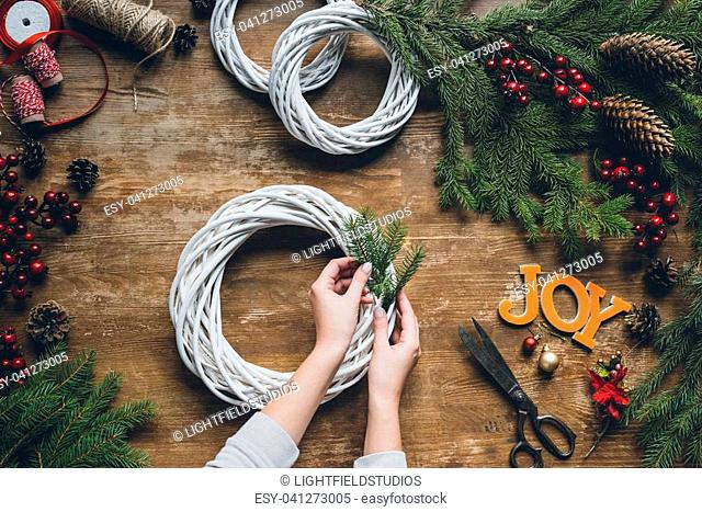 top view of female hands making Christmas wreath with fir branches and word Joy on wooden tabletop