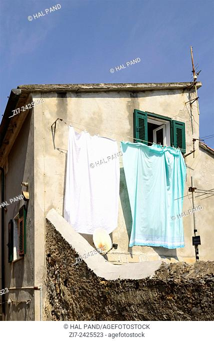 view of old facade with sharp contrast between traditional hanging laundry in the sun and satellite dish, Portovenere, Italy