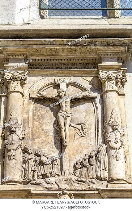 Jesus Christ on the cross, details of architecture on Mariacki church in Krakow, Poland