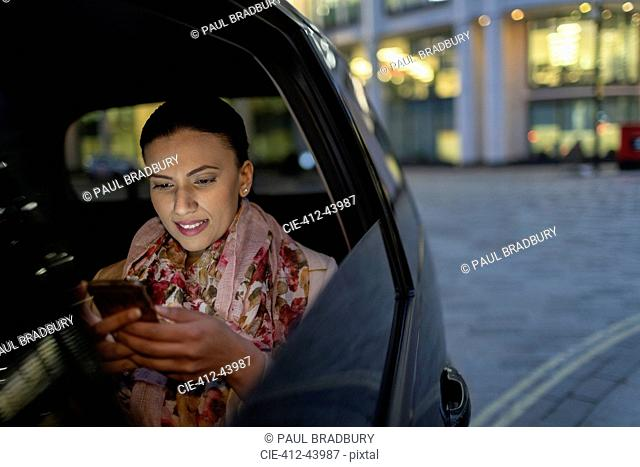 Businesswoman using smart phone in crowdsourced taxi at night