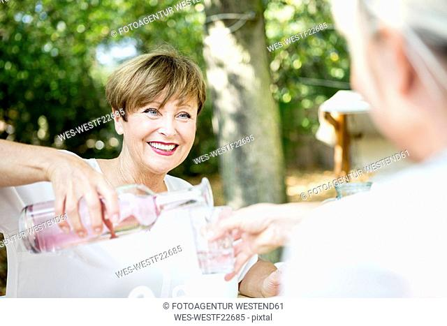 Smiling senior woman pouring water into friend's glass