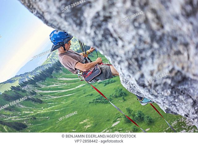 man climbing and preparing backup anchor point for stretching the highline slackline rope in Bavarian alps, near mountain Blankenstein, south of Germany