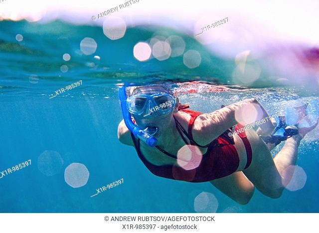 Underwater view of a young woman snorkeling