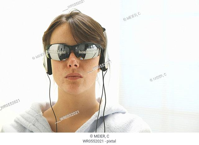 portrait of a young woman wearing glasses and headset Brainlight - brainlight - brain light