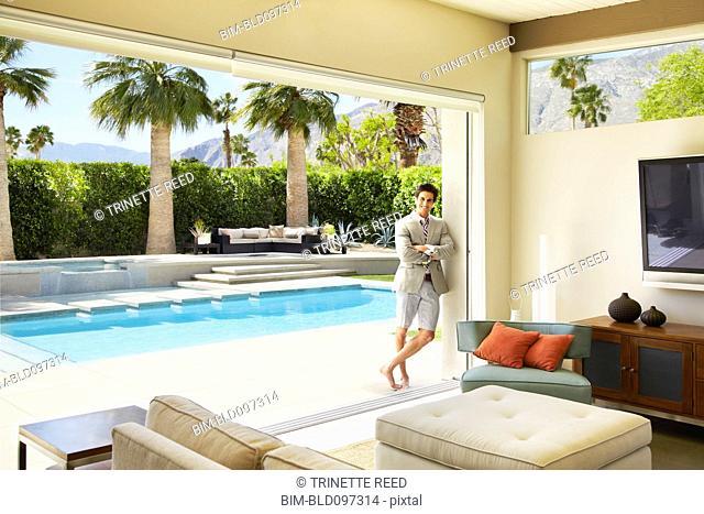 Trendy Caucasian man leaning against wall near swimming pool