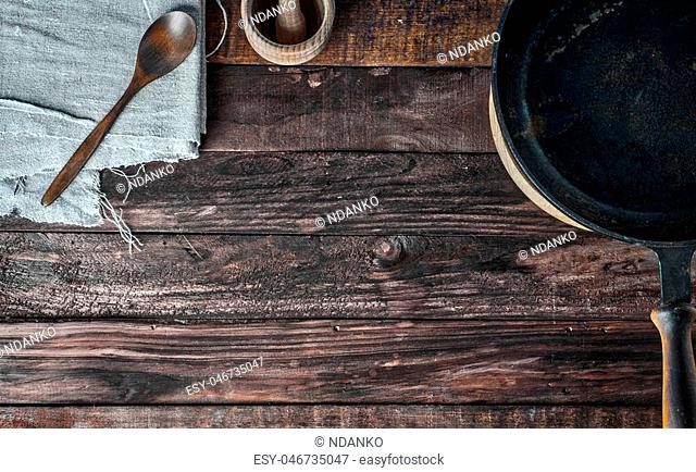 Brown wooden background with black frying pan and wooden spoon, empty space in the middle, top view