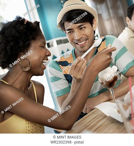 A young man and woman sharing an ice cream sundae