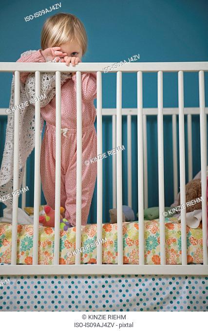 Portrait of female toddler hiding behind comfort blanket in crib