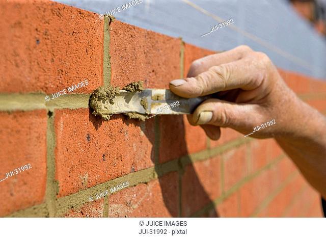 Close up of bricklayer applying mortar between bricks in wall