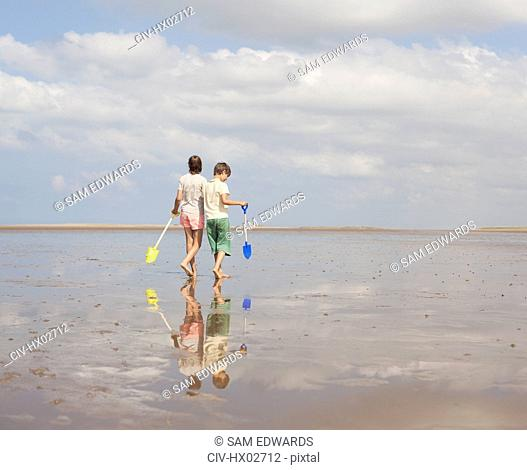 Brother and sister walking with shovels in wet sand on sunny summer beach