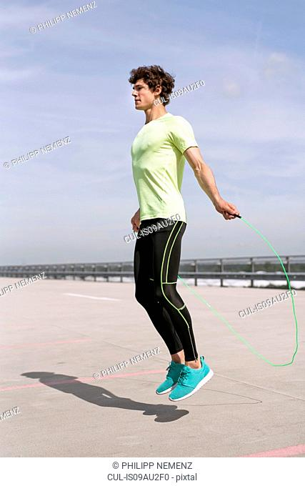 Young man exercising with skipping ropes in city