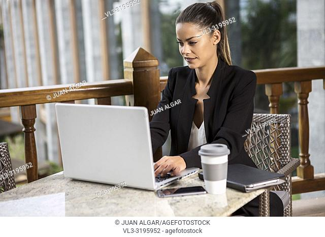 Beautiful trendy businesswoman in black suit sitting with coffee at table and surfing laptop