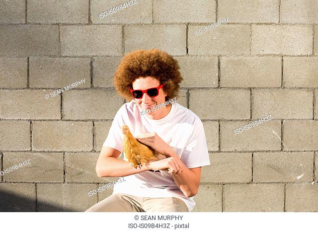 Portrait of teenage boy with red afro hair, holding chicken