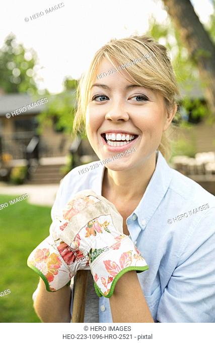 Portrait of enthusiastic woman wearing gardening gloves