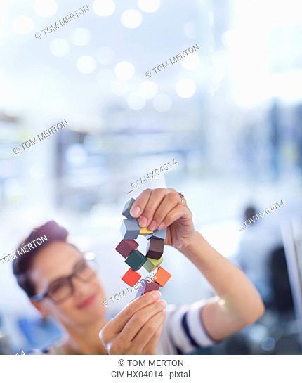 Curious, innovative female entrepreneur examining prototype