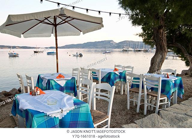 Table and chairs on the waterfront at sunset, Adamas, Milos Island, Dodecanese, Greece