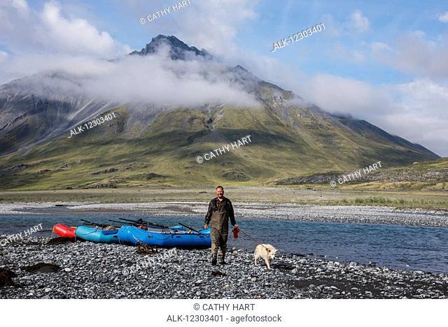 Man walks his dog along the Marsh Fork of the Canning River in the Arctic National Wildlife Refuge, Summer, Alaska