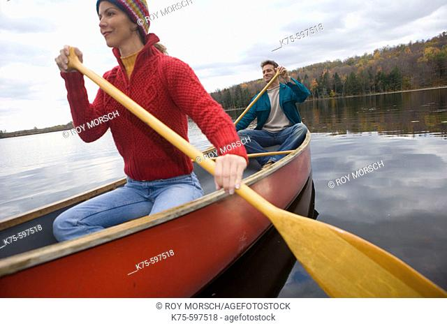 Couple canoe on lake in the fall