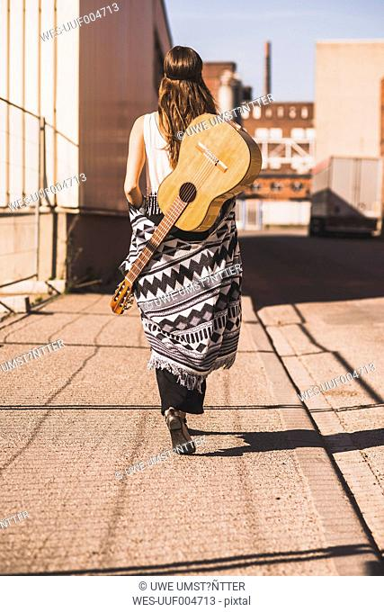 Young woman with guitar on her back walking on street