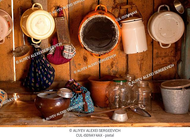 Traditional wood kitchen with saucepans, jars and utensils on shelf