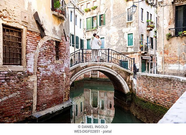 Italy, Venice, bridal couple standing on little bridge