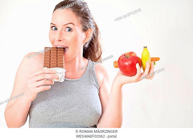 Pregnant woman eating bar of chocolate, portrait